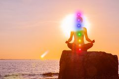Woman is meditating with glowing seven chakras on stone at sunset. Silhouette of woman is practicing yoga on the beach. Woman is meditating with glowing seven royalty free stock photo