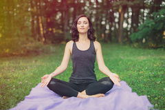 Woman meditating in a green field with trees Royalty Free Stock Images