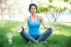 Woman meditating on the green grass Stock Images