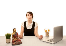 Woman meditating at her desk Stock Photo