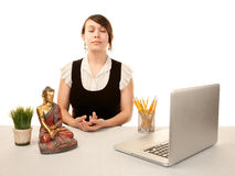 Woman meditating at her desk. Pretty young woman meditating at her desk Stock Image