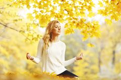 Woman Meditating In Autumn Park Royalty Free Stock Image
