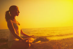 Woman Meditating In Lotus Pose On The Beach At Sunset Royalty Free Stock Photos