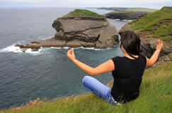 Woman meditating on irish cliffs Royalty Free Stock Images