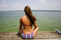 Woman meditating on lake. Side Royalty Free Stock Images