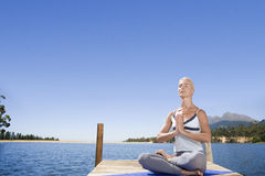 Woman meditating on lake dock Stock Image