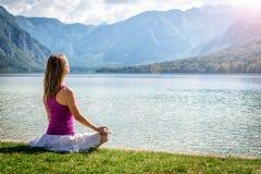 Woman meditating at the lake Stock Photos