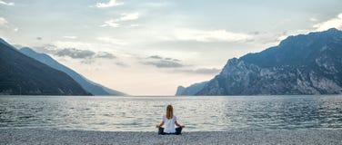 Woman meditating at the lake Royalty Free Stock Images
