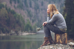 Woman meditating on a lake shore. Horizontal side view portrait of Caucasian young blonde woman with light colored sweater and jeans holding a tree branch and Royalty Free Stock Images