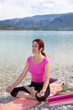 Woman meditating on a lakeshore. Royalty Free Stock Photo