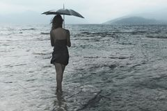 Woman meditating looking at infinity in the rain and thunderstorm. Lonely woman meditating looking at infinity in the rain and thunderstorm Stock Images
