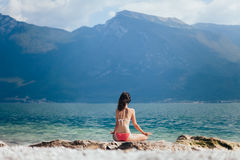Woman meditating in Lotus Pose on beautiful beach of mountain la Royalty Free Stock Photography