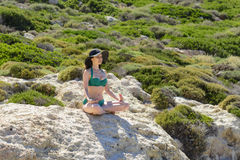 Woman meditating in Lotus pose on the cliffs of the beautiful beach of Balos, Greece. the concept of rest, relaxation, spiritual p. Eace, qigong Royalty Free Stock Images