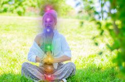 Woman is meditating in the lotus pose with glowing seven chakras on grass. Woman is practicing yoga on the park. Happy woman is meditating in the lotus pose with stock images