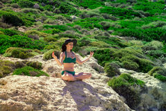 Woman meditating in Lotus pose on the rocks. the concept of rest, relaxation, spiritual peace, yoga. Stock Image