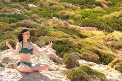 Woman meditating in Lotus pose on the rocks. the concept of rest, relaxation, spiritual peace, yoga. Stock Photos