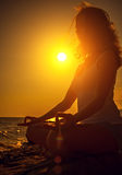 Woman meditating in lotus pose  at sunset Stock Photography