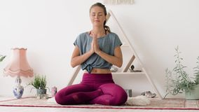 Woman meditating in lotus pose at yoga studio. Mindfulness, spirituality and healthy lifestyle concept - woman meditating in lotus pose at yoga studio stock footage
