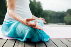 Woman meditating in the lotus position closeup. Hands close-up mudra. Sitting on wooden floor by the river Royalty Free Stock Photo