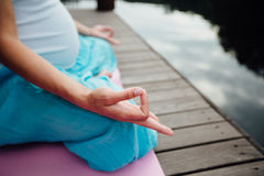 Woman meditating in the lotus position closeup. Hands close-up mudra. Sitting on wooden floor by the river Royalty Free Stock Photography