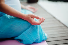 Woman meditating in the lotus position closeup. Hands close-up mudra. Sitting on wooden floor by the river Stock Photography