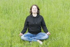 Woman meditating in the lotus position on the green grass Royalty Free Stock Images