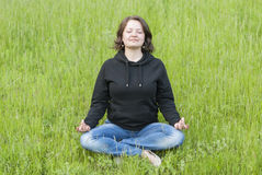 Woman meditating in the lotus position on the green grass Stock Photos