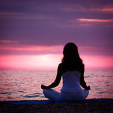 Woman Meditating in Lotus Position by the Sea. Silhouette of Woman Meditating in Lotus Position by the Sea at Sunset. Rear View. Nature Meditaion Concept. Toned Stock Images
