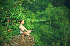 Woman meditating in lotus posture, doing yoga on top of the moun. Tain on a rock in nature in the forest Royalty Free Stock Photos