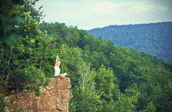 Woman meditating in lotus posture, doing yoga on top of the mountain Royalty Free Stock Photo
