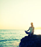 Woman meditating in  lotus yoga on beach Stock Photo
