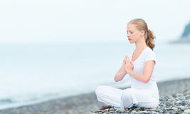 Woman meditating in  lotus yoga on beach Stock Image