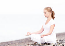 Woman meditating in  lotus yoga on beach Stock Photos