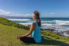 Woman Meditating on Maui. A woman practicing yoga along the scenic coast of Maui Hawaii Royalty Free Stock Photos