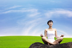 Woman meditating in meadow Stock Photography