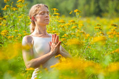 Woman meditating in meadow of yellow flowers Royalty Free Stock Images