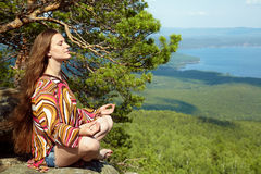 Woman meditating at mountains. Young beautiful woman meditating at the mountains. relaxation outdoors. nature freedom and inspiration Stock Images