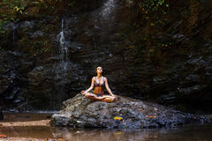 Woman meditating in nature waterfall on the rock in forest Royalty Free Stock Images