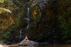 Woman meditating in nature waterfall on the rock Royalty Free Stock Images