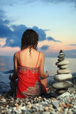 Woman meditating near to pyramid from pebble Stock Photo