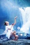 Woman meditating near waterfall Royalty Free Stock Image
