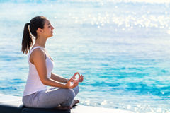 Woman meditating next to sea. Full length portrait of young woman meditating next to sea. Side view of girl doing yoga exercise in early morning sun with bright Stock Photo
