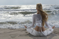 Woman Meditating By The Ocean Stock Photo