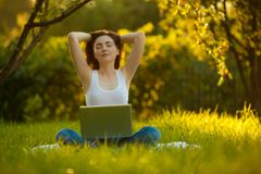 Woman meditating at the park with laptop royalty free stock photos