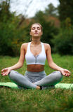 Woman meditating in park, sitting with eyes closed Royalty Free Stock Photo