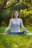 Woman meditating at the park Stock Photography