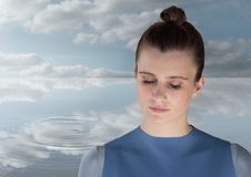 Woman Meditating peacefully by water ripple of clouds Royalty Free Stock Image