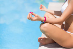 Woman meditating by the pool Stock Photography