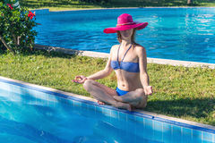 Woman meditating at the pool Stock Photo