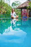 Woman meditating at pool side Royalty Free Stock Photo